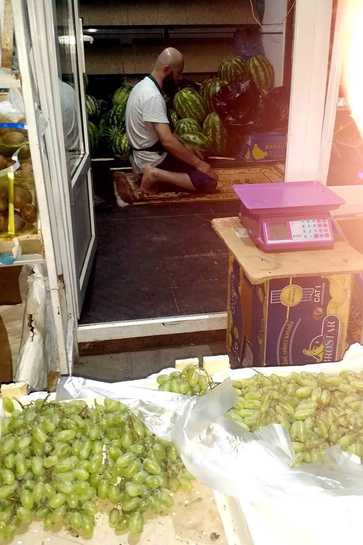 Islam im Alltag. Ein Gemüseverkäufer in Almaty in Kasachstan betet in seinem Laden © Edda Schlager
