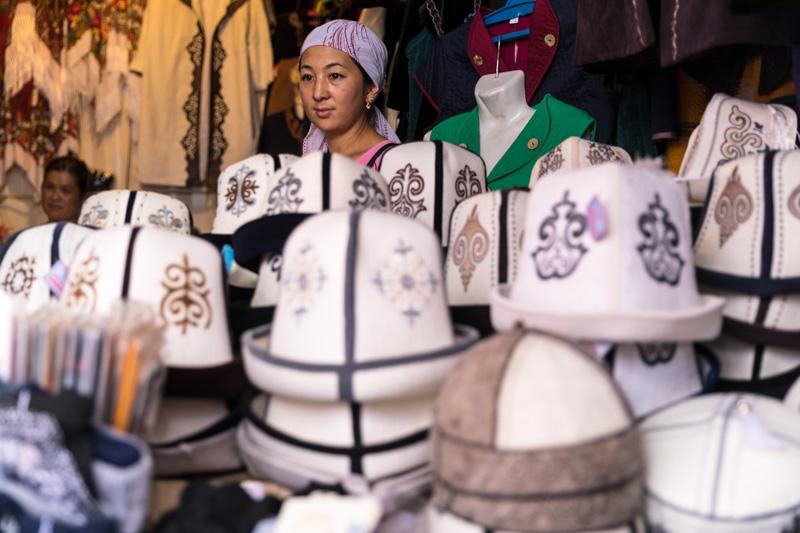 Verkäuferin kirgisischer Filzhüte auf dem Basar in Osch